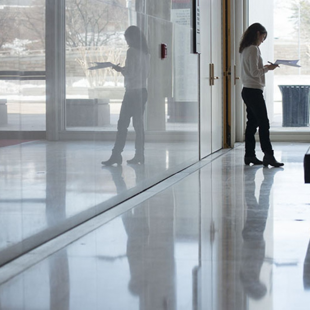 photo of woman in hallway looking at papers