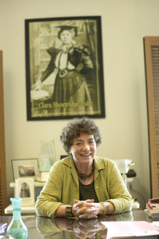 photo of Babcock seated at desk before large portrait of Clara Foltz